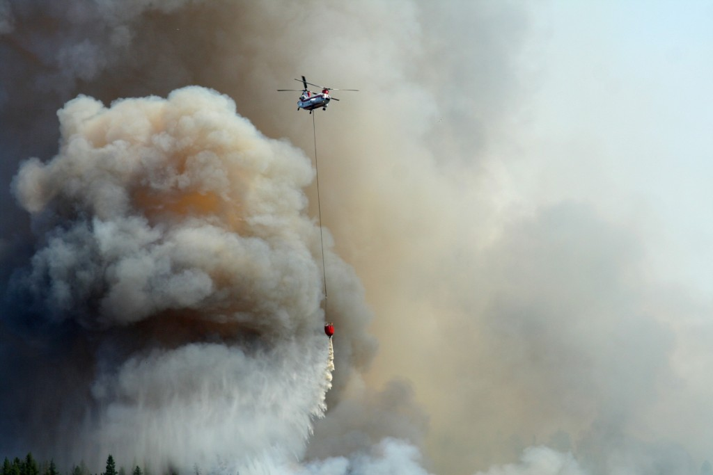 A helicopter releases fire-suppressant chemicals on a forest fire.